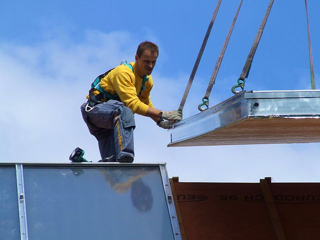 Installation av solpaneler. Foto: Stefan Thiesen. Licensierad under CC BY-SA 3.0 via Wikimedia Commons - https://commons.wikimedia.org/wiki/File:Installation_of_%22Solar_roof%22_solar_thermal_installation_for_small_district_heating_plant_serving_several_homes.jpg#/media/File:Installation_of_%22Solar_roof%22_solar_thermal_installation_for_small_district_heating_plant_serving_several_homes.jpg